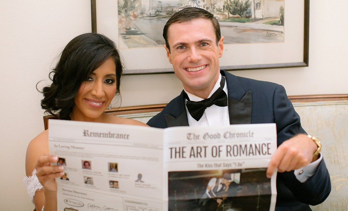 couple posing with their own wedding newspaper program