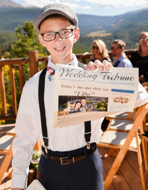 paperboy at wedding holding wedding program newspaper